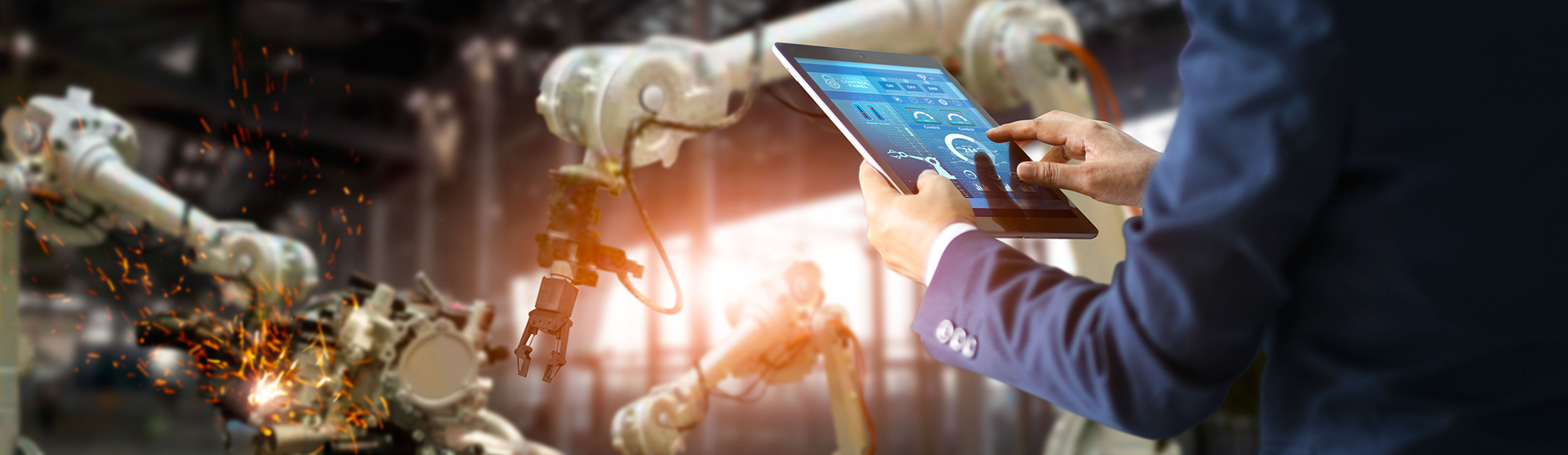 User with tablet in front of industrial robots.